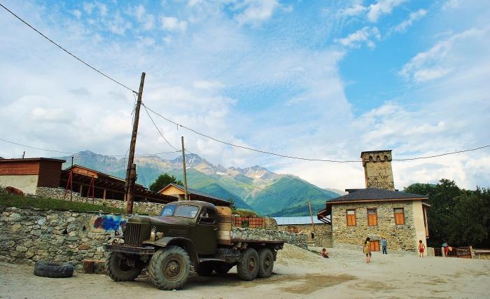 Gruzja; Mestia - ciężarówka na tle gór i tradycyjnej wieży.